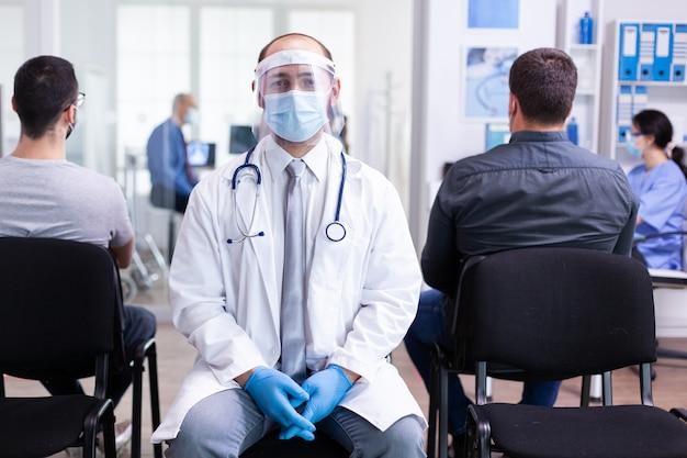 Lekarz z wizjerem przeciwko koronawirusowi w poczekalni, patrząc na kamerę intro