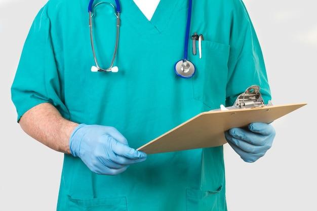 Lekarz z zielonym mundurem i klipsem w rękach z rękawiczkami chirurgicznymi
