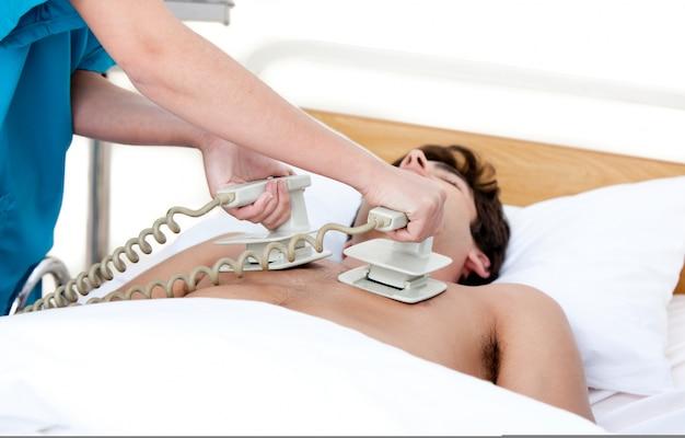 Lekarz za pomocą defibrylatora, aby reanimować nieprzytomnego patie