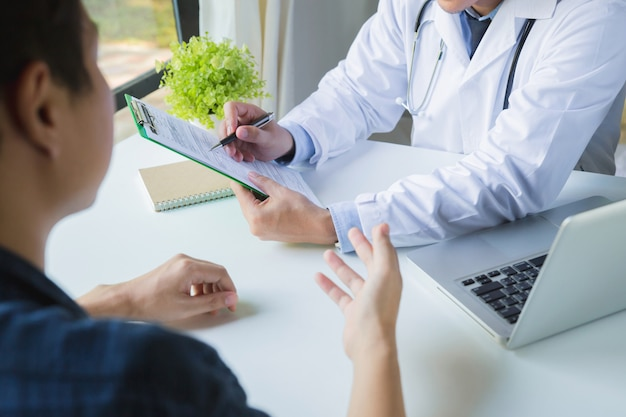 Lekarz za pomocą schowka, aby wypełnić historię medyczną leku młodego mężczyzny. lekarz i pacjent omawiając wyniki badania fizykalnego w klinice