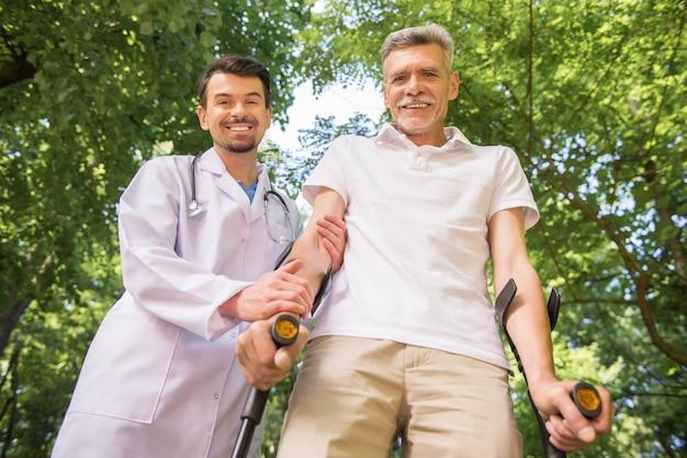 Lekarz zachęcając jego pacjenta do chodzenia z kulami.