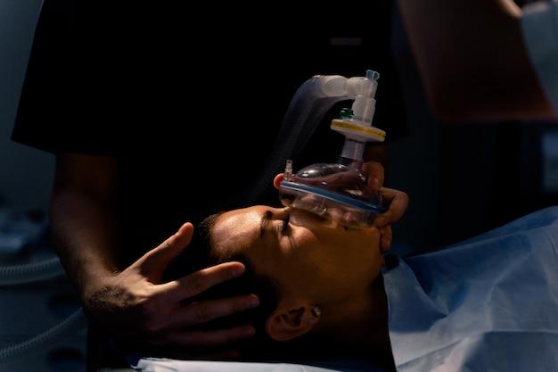 Lekarz zakłada maskę do sztucznej wentylacji płuc na oddziale intensywnej terapii