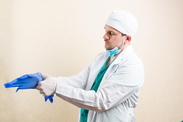 Lekarz zakłada rękawiczki. na jasnym tle. zdjęcie wysokiej jakości