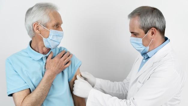 Lekarz zakładający bandaż na pacjenta płci męskiej po podaniu zastrzyku szczepionki