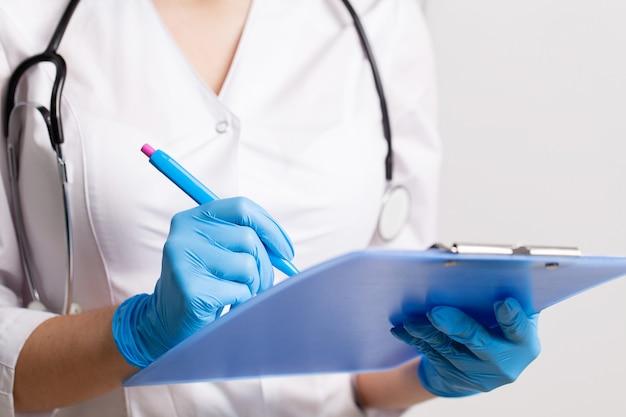 Lekarz zapisuje historię medyczną pacjenta za pomocą pióra na karcie.