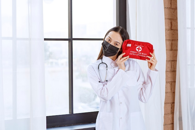 Lekarz Ze Stetoskopem I Czarną Maską Trzyma Czerwoną Apteczkę. Premium Zdjęcia