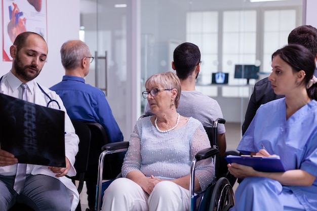 Lekarz ze stetoskopem komunikujący się z niepełnosprawną starszą kobietą w badaniu radiologicznym w wyniku testu na wózku inwalidzkim, siedząc w poczekalni szpitalnej