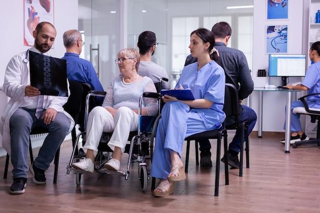 Lekarz ze stetoskopem rozmawiający i wskazujący na radiografię niepełnosprawnej staruszki na wózku inwalidzkim.
