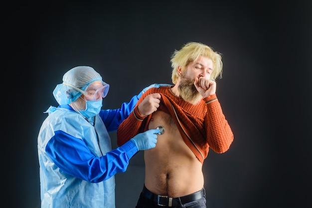 Lekarz ze stetoskopem słucha płuc pacjenta. lekarz bada człowieka ze stetoskopem.