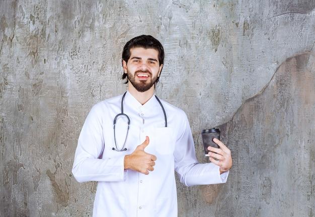 Lekarz ze stetoskopem trzymający czarną jednorazową filiżankę napoju i cieszący się chwilą lub produktem.