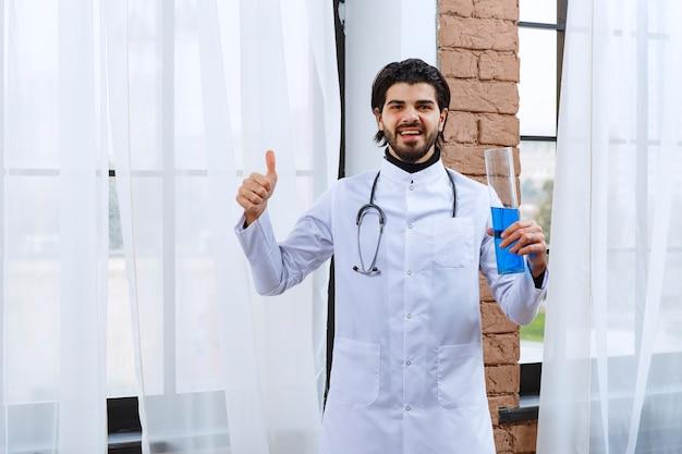 Lekarz ze stetoskopem trzymający kolbę chemiczną z niebieskim płynem w środku i pokazując kciuk do góry.