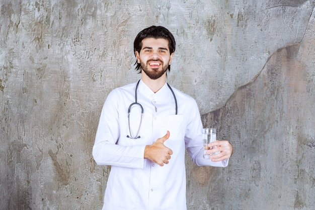 Lekarz ze stetoskopem trzymający szklankę czystej wody i pokazujący pozytywny znak ręki