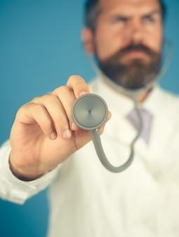 Lekarz ze stetoskopem w ręku koncentruje się na sprzęcie szpitalnym stetoskopu diagnostycznego