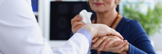 Lekarz ze współczuciem trzyma rękę starszego pacjenta