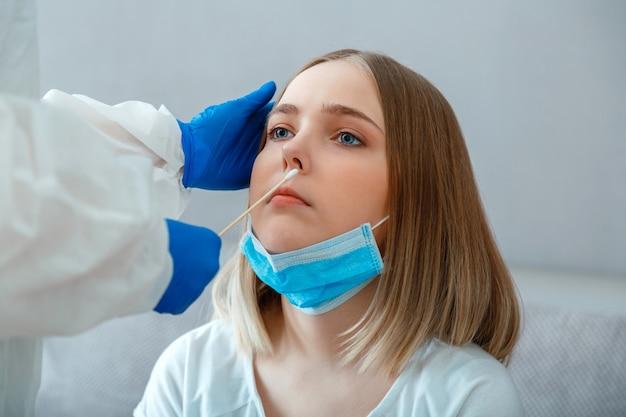 Lekarz zrobić test pcr do kobiety pacjenta. pielęgniarka pobiera próbkę śliny przez nos bawełnianym wacikiem, aby sprawdzić koronawirusa covid 19. pracownik medyczny w masce ochronnej wykonuje test pcr w domu lub w klinice.