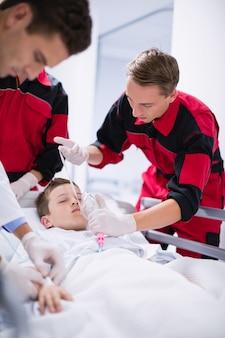 Lekarze dostosowujący maskę tlenową podczas spieszenia pacjenta w pogotowiu