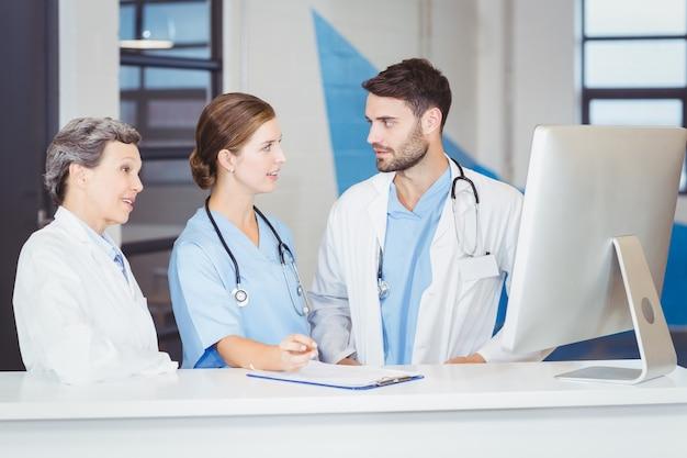 Lekarze dyskutuje przy biurku komputerowym