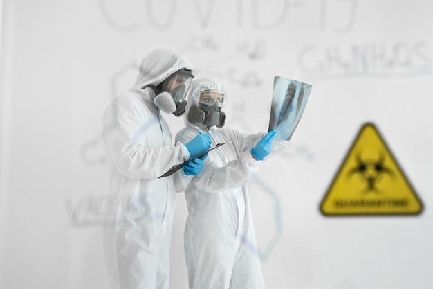 Lekarze epidemiolodzy badają promieniowanie rentgenowskie w kierunku zapalenia płuc pacjenta z covid-19. koncepcja koronawirusa. lekarz w mundurze ppe oblicza formułę wirusa
