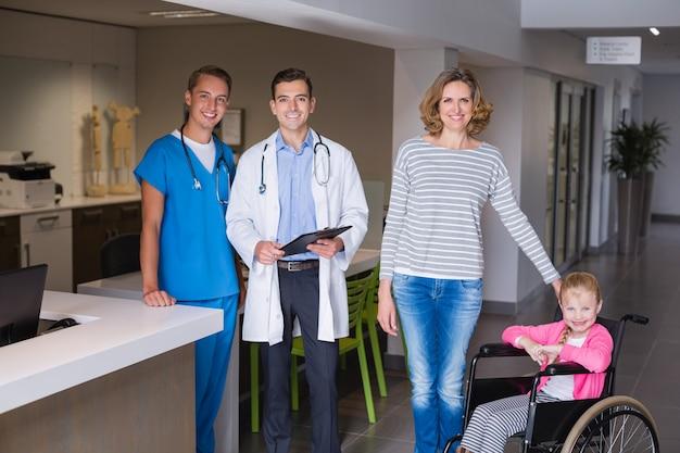 Lekarze i kobiety stojącej z niepełnosprawną dziewczynę w korytarzu