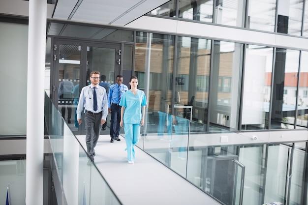 Lekarze i pielęgniarka spacerujący po korytarzu