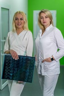 Lekarze kobiet posiadających prześwietlenie w nowoczesnej sali medycznej z tomografią komputerową.