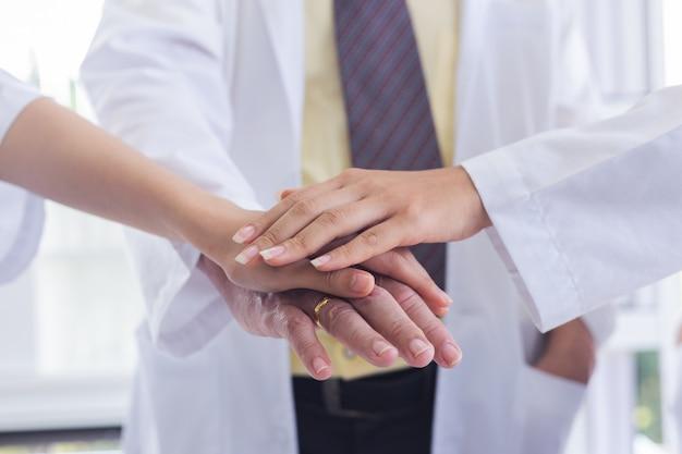 Lekarze łączą ręce razem i koncepcja pracy zespołowej.