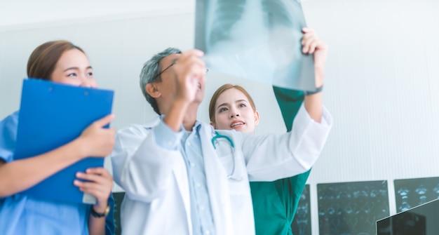Lekarze medycyny patrzeje promieniowania rentgenowskiego w szpitalu