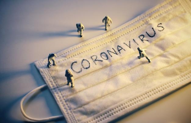 Lekarze miniaturowi z ochronnym kombinezonem zapobiegającym pandemii covid-19 i koronawirusa
