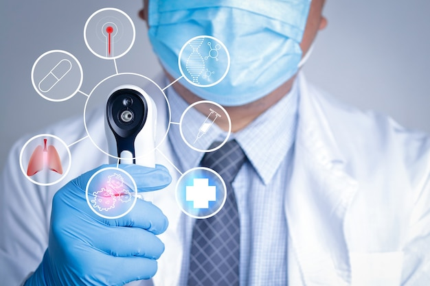 Lekarze noszą maskę i rękawiczki, trzymają cyfrowy termometr, aby zbadać pacjenta. pokaż grafikę, obróbkę, montaż.