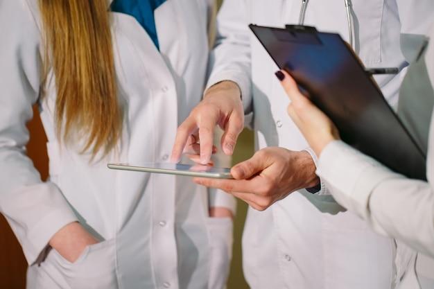 Lekarze omawiający kardiogram pacjenta na tablecie.