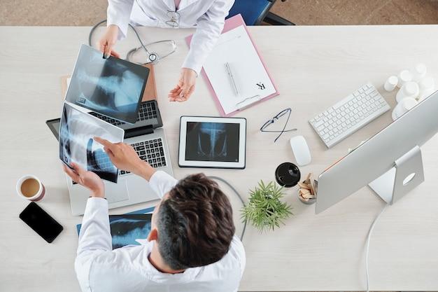 Lekarze omawiający prześwietlenia klatki piersiowej