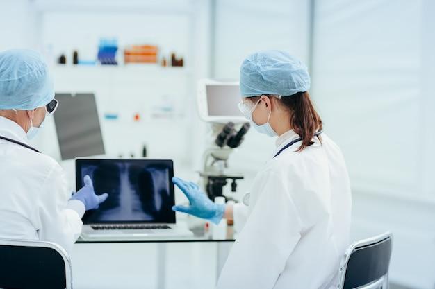 Lekarze omawiający prześwietlenie klatki piersiowej.
