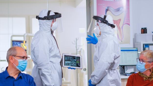 Lekarze ortodonci z osłoną twarzy i kombinezonem ppe dyskutują w recepcji o cyfrowym prześwietleniu zębów za pomocą tabletu podczas globalnej pandemii. koncepcja nowej normalnej wizyty u dentysty w epidemii koronawirusa.