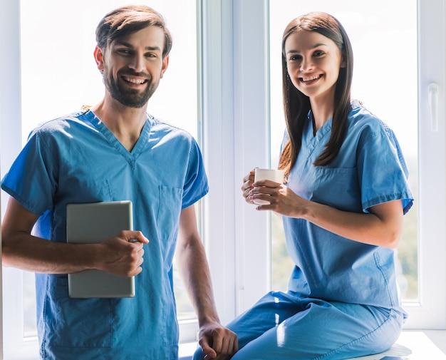 Lekarze patrzą na aparat i uśmiechają się.