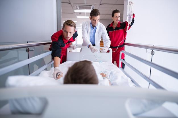 Lekarze pchają nosze awaryjne na korytarzu