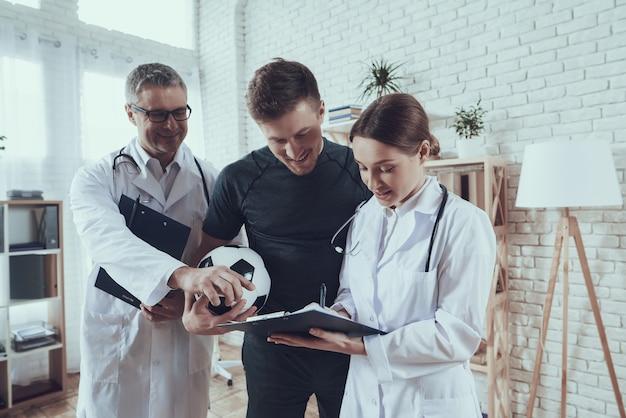 Lekarze płci męskiej i żeńskiej rozmawiają z piłkarzem