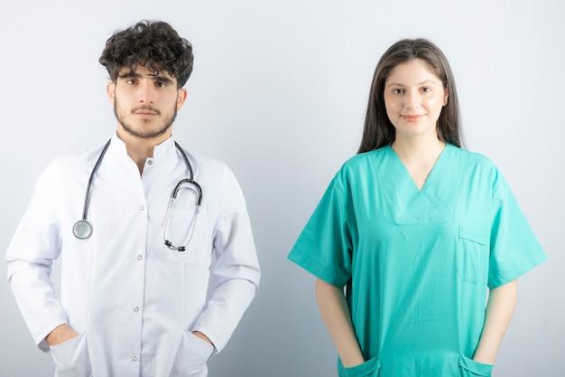 Lekarze płci męskiej i żeńskiej stojąc i patrząc na kamery.