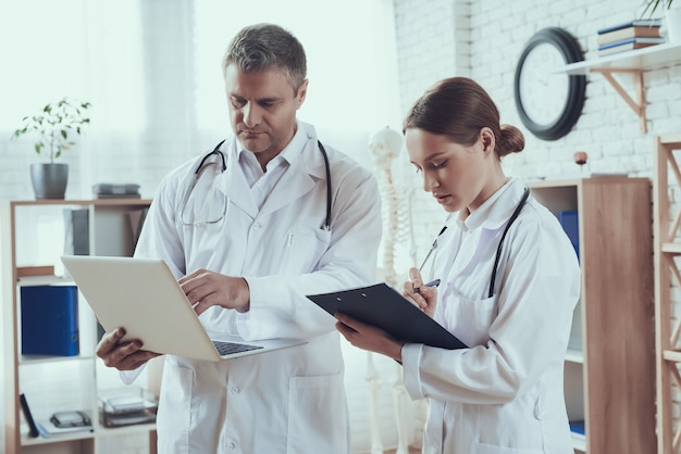 Lekarze płci męskiej i żeńskiej w białych fartuchach ze stetoskopami.