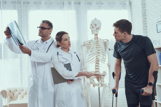 Lekarze pokazują miednicę rannemu sportowcowi.