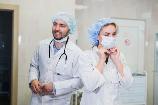 Lekarze przygotowujący przy pomocy akcesoriów ochronnych
