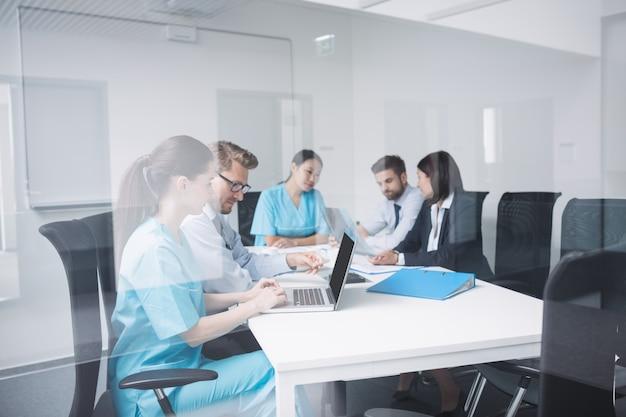 Lekarze rozmawiają przy laptopie na spotkaniu