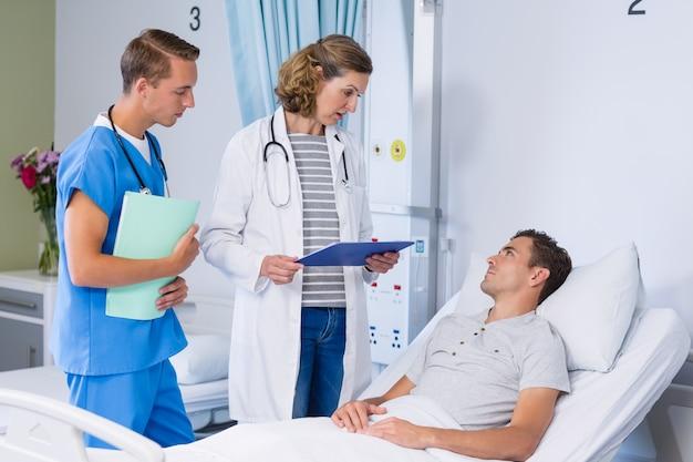 Lekarze rozmawiają z pacjentem w łóżku szpitalnym