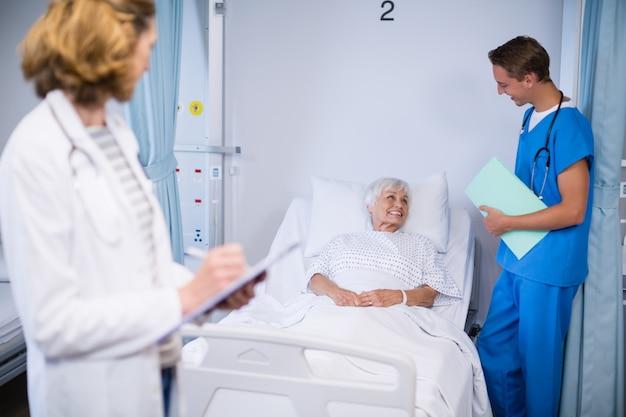 Lekarze rozmawiają ze starszym pacjentem