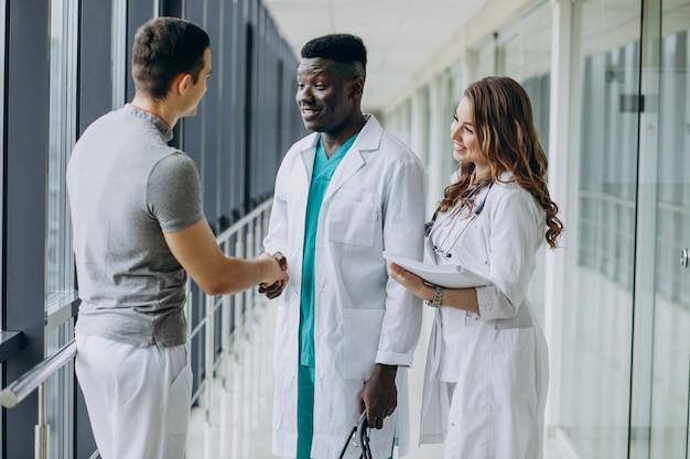 Lekarze ściskają ręce pacjentowi, stojąc na korytarzu szpitala