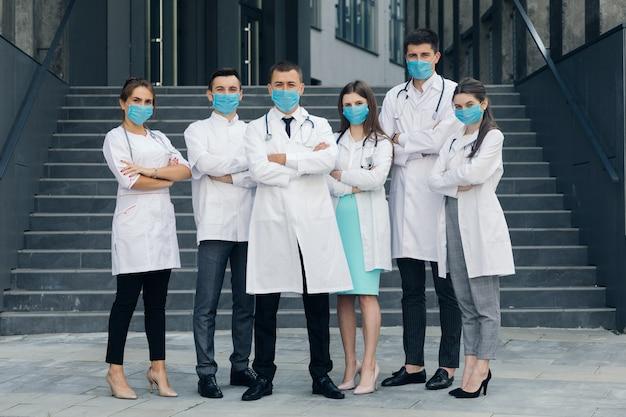 Lekarze stoją ze skrzyżowanymi rękami, nosząc ochronne maski na twarz na zewnątrz podczas epidemii covid-19 i patrzenia na kamerę.
