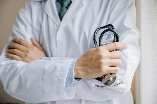 Lekarze stojąc prosto z rękami skrzyżowanymi w szpitalu.