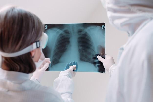 Lekarze stojący na białej ścianie badają prześwietlenie w kierunku zapalenia płuc pacjenta covid-19 w klinice. koncepcja koronawirusa.