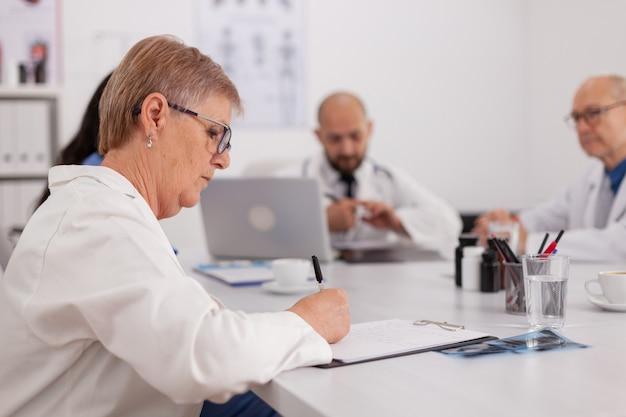 Lekarze szpitalni pracujący przy prezentacji wiedzy medycznej, przepisujący leki w pigułkach siedzący przy biurku w sali konferencyjnej. planowanie pracy zespołowej leczenia