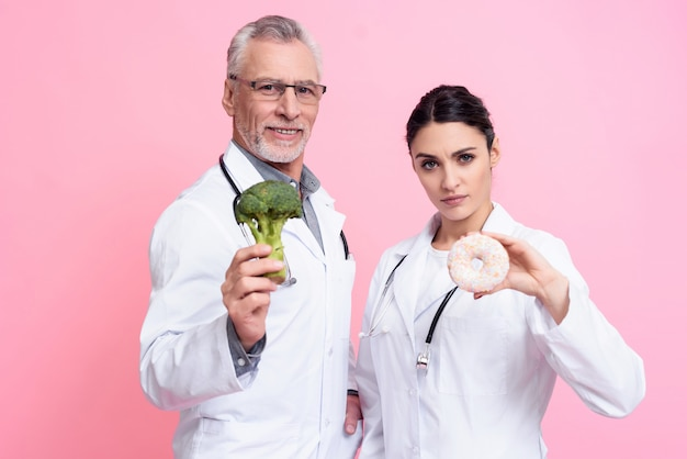 Lekarze trzymają brokuły i pączki.
