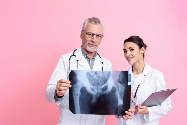 Lekarze trzymają promieniowanie rentgenowskie i schowka na białym tle.